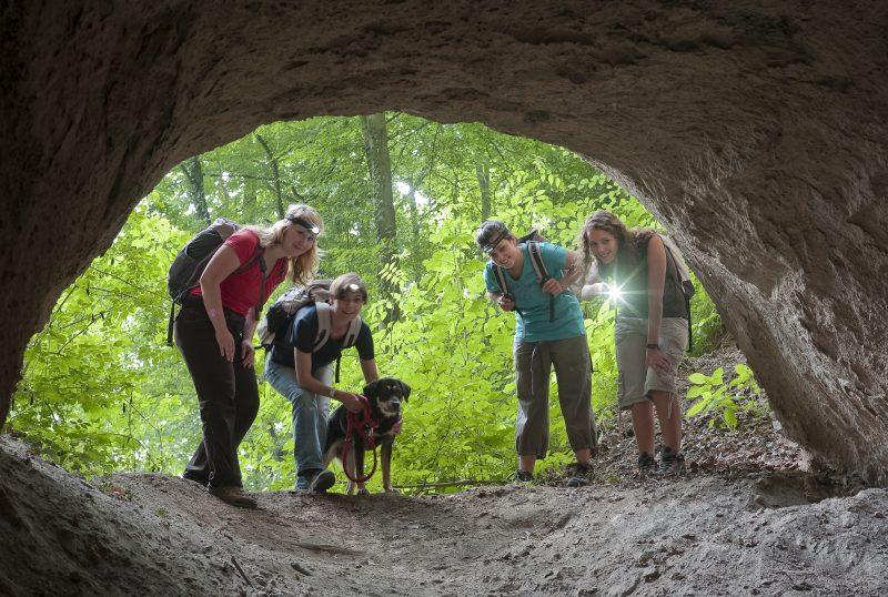 Jugendliche Wanderer blicken in die Höhle
