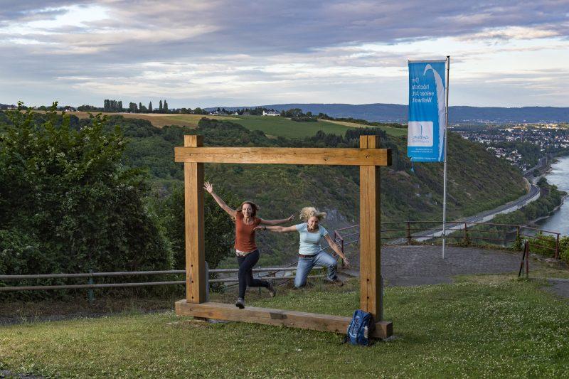 Zwei Wanderer springen aus Holzrahmen