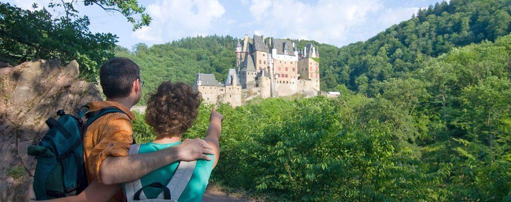 Wanderer schauen auf Burg Eltz