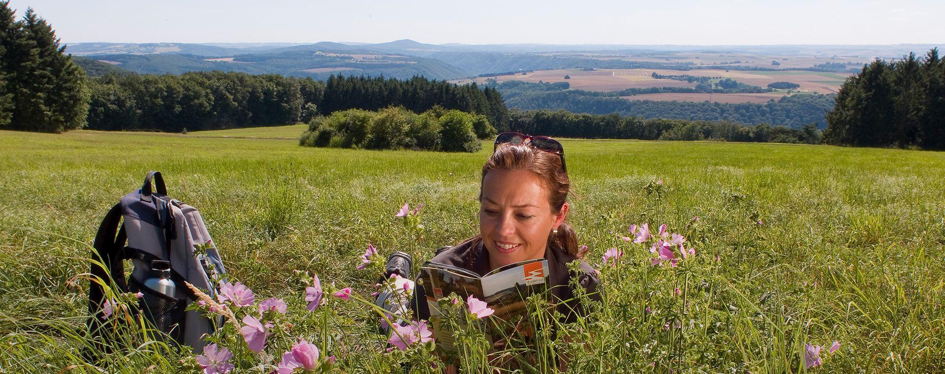 Frau liegt im Gras mit Traumpfade-Flyer