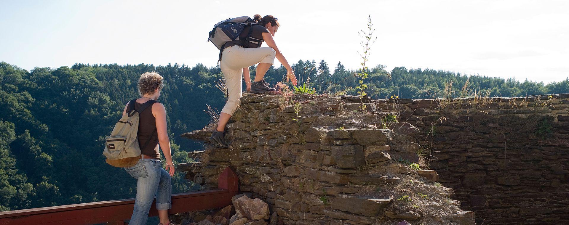 Wanderer klettert auf Ruine